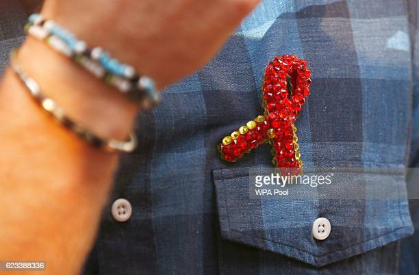 Prince Harry receives a specially made red brooch from a member of the 'Joyful Noise' choir a creation of NAZ a sexual health charity for minority...