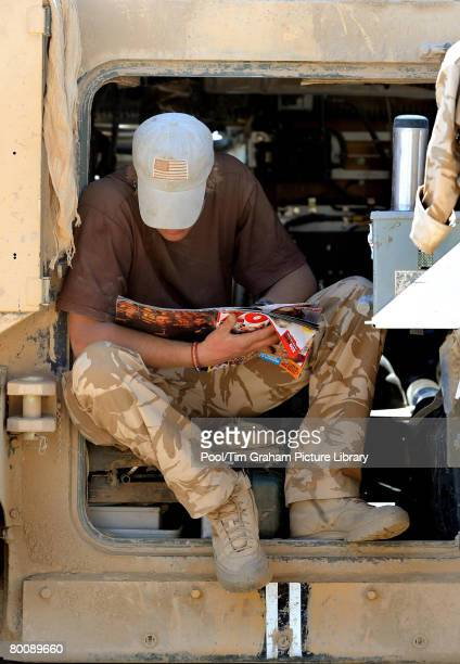 Prince Harry relaxes in the door to his Spartan armoured vehicle reading a copy of Zoo magazine in Helmand province on February 19 2008 in Southern...