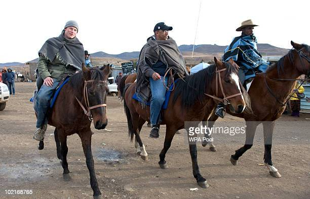 Prince Harry rides into Semongkong in Lesotho with Prince Seeiso from Lesotho to visit a classroom and watch a lesson lit by oil lamps for Herd Boys...