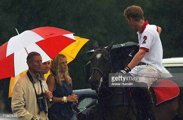 Prince Harry rides up on his polo pony to chat with girlfriend Chelsy Davy and his father Prince Charles Prince of Wales in torrential rain at...