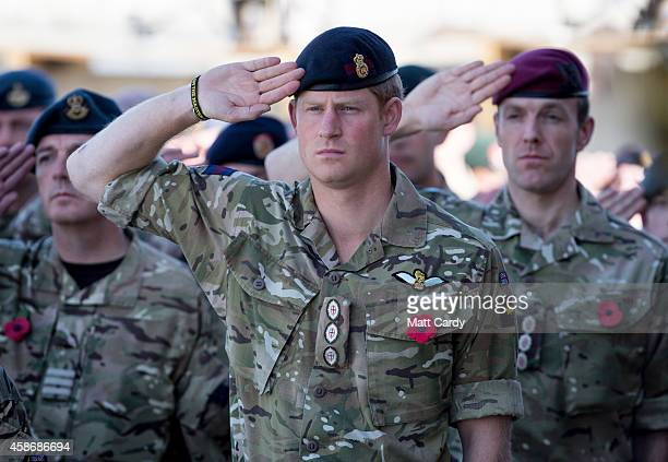 Prince Harry salutes as the Last Post is played as he joins British troops and service personal remaining in Afghanistan and also International...