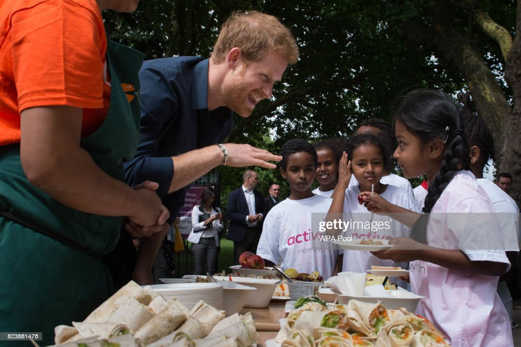 Prince Harry serves food to children during a visit to StreetGames' Fit and Fed at Central Park East Ham on July 28, 2017 in London, England. The session which forms part of the Fit and Fed campaign aims to provide children and young people with access to activity sessions during the summer.