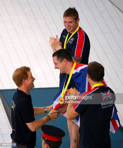 Prince Harry shakes hands with gold medalist Michael Goody of Great Britain after presenting him with his medal next to silver medalist Luke Reeson...