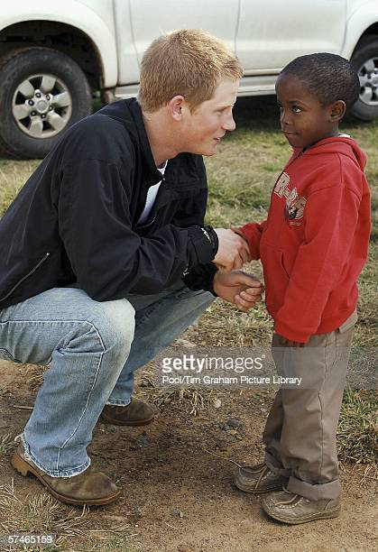 Prince Harry shakes hands with his old friend Mutsu Potsane in the grounds of the Mants'ase children's home while on a return visit to Lesotho in...