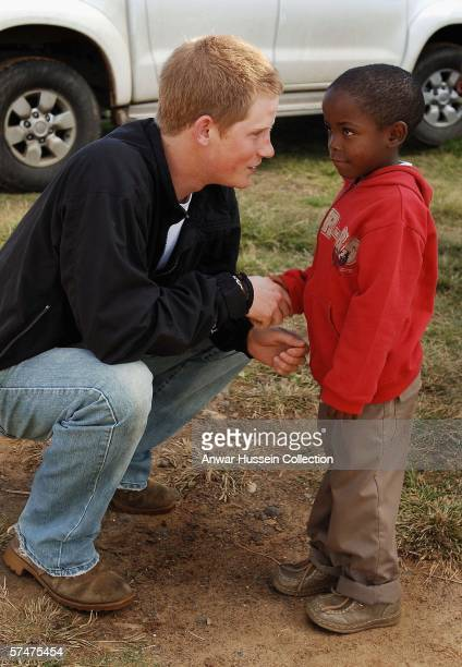 Prince Harry shakes hands with Mutsu Potsane in the grounds of the Mants'ase children's home while on a return visit to Lesotho on April 24, 2006 in...