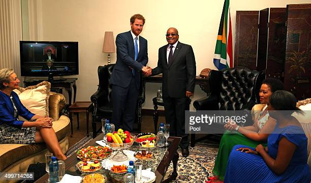Prince Harry shakes hands with South African President Jacob Zuma watched by his wife and daughter Tobeka Madiba Zuma and Msholozi Zumaseen and the...