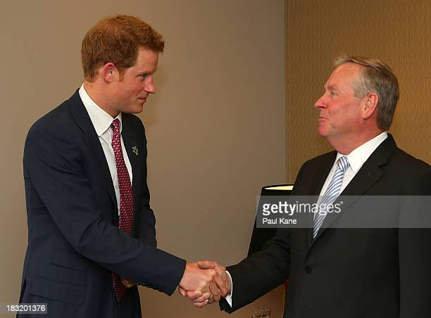 Prince Harry shakes hands with West Australian Premier Colin Barnett after arriving at Perth Airport on October 6 2013 in Perth Australia Prince...