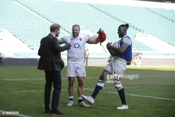 Prince Harry shares a joke with England rugby players James Haskell and Maro Itoje as he attends the England rugby team's open training session as...