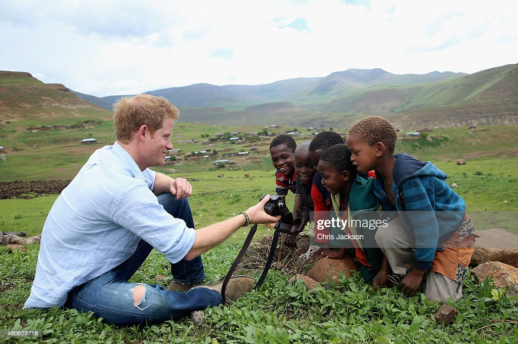 Prince Harry shows children a photograph he has taken on a Fuji X100s Camera during a visit to a herd boy night school constructed by Sentebale on December 8, 2014 in Mokhotlong, Lesotho. Prince Harry was visiting Lesotho to see the work of his charity Sentebale. Sentebale provides healthcare and education to vulnerable children in Lesotho, Southern Africa. Speaking of the opportunity to document the visit himself, Prince Harry said: 'I have always enjoyed photography and the challenges that come with trying to capture the perfect shot, although privately I don't take many photos. The best photos I have are in my head - I have some very special memories, mostly from Africa. But on this visit, I had the time and opportunity to be on the other side of the camera and take some photos in the stunning country of Lesotho for my charity Sentebale.'