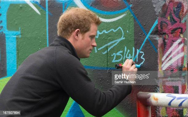 Prince Harry signs his name on a large graffiti 'Harry' sprayed on a wall as he visits the Russell Youth Club during an official visit to Nottingham...