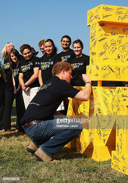 Prince Harry signs the Invictus Games logo during the Jaguar Land Rover Driving Challenge at Jaguar Land Rover Engineering Centre on September 9 2014...