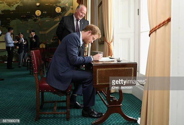 Prince Harry signs the visitors book as he attends a reception for Normandy Veterans at Southwick House on June 2, 2016 in Portsmouth, England. The...