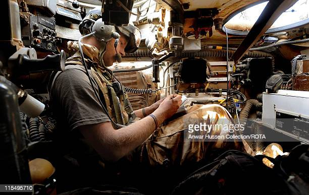 Prince Harry sits below the turret of his Spartan armoured vehicle as he communicates by radio to other units in the desert on February 20, 2008 in...