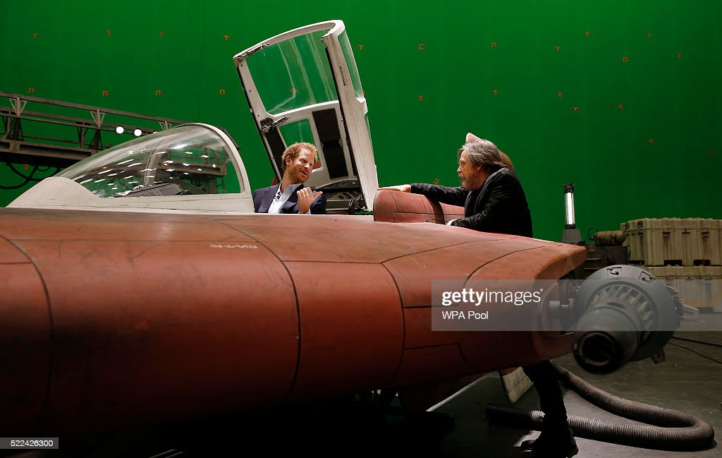 Prince Harry (L) sits in an A-wing fighter as he talks with US actor Mark Hamill during a tour of the Star Wars sets at Pinewood studios on April 19, 2016 in Iver Heath, England. Prince William and Prince Harry are touring Pinewood studios to visit the production workshops and meet the creative teams working behind the scenes on the Star Wars films.