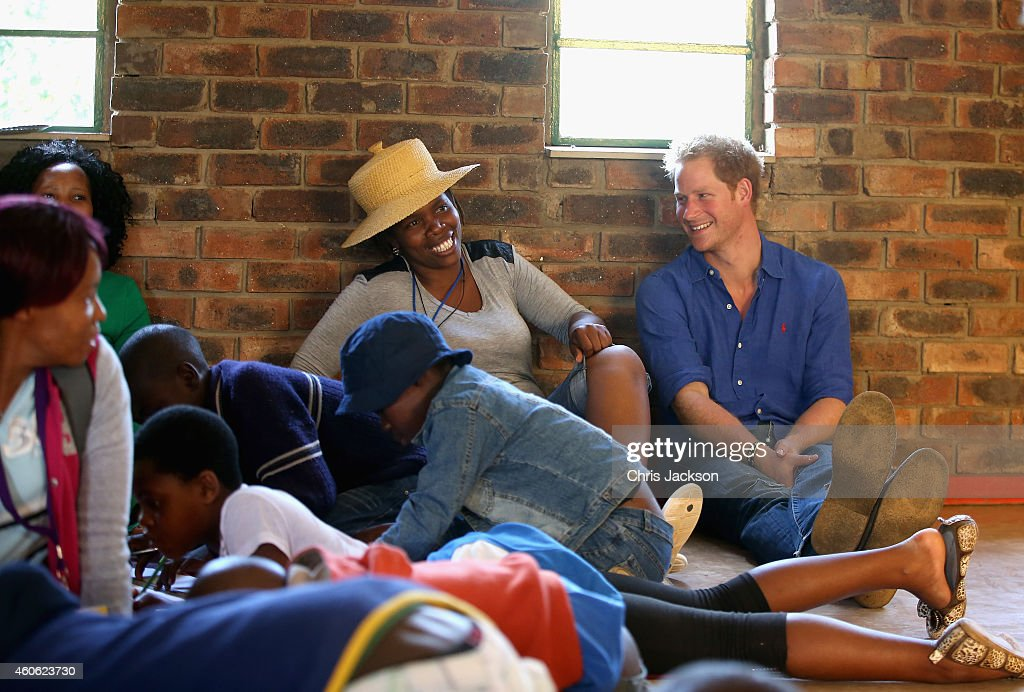 Prince Harry sits next to a volunteer who was laughing at his singing during a visit to a Mamohato Network Club for children living with HIV at St Paul Centre on December 9, 2014 in Maseru, Lesotho. Prince Harry was visiting Lesotho to see the work of his charity Sentebale. Sentebale provides healthcare and education to vulnerable children in Lesotho, Southern Africa. Prince Harry said 'A chance to see one of the camps in full swing. Normally when we visit Lesotho, it's school time and therefore we always miss the Camp Mamohato. 44 children, from all over Lesotho gathered for a week of fun and learning about living with HIV. These are children who have never had the chance to talk about their illness, and who had no idea that they were one of so many in their age group. It was really emotional watching them interact with each other. Some really outgoing chatty kids, others slightly overwhelmed, but all with huge smiles. This confirmed to me again that what we're doing is going to change thousands of children's lives, and hopefully save a generation.'
