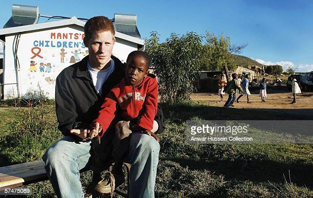 Prince Harry sits with an old friend Mutsu Potsane in the grounds of the Mants'ase children's home while on a return visit to Lesotho on April 24,...