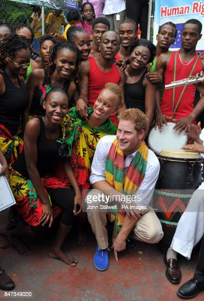 Prince Harry sits with dancers and musicians during a visit to the Rise Life charity project in Jamaica as part of a Diamond Jubilee tour where he is...
