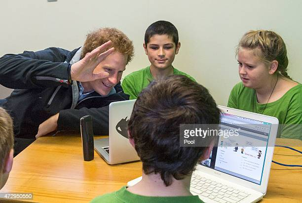 Prince Harry sits with pupils as they take part in a German lesson on Skype at Halfmoon Bay School in Oban as he leaves on May 11 2015 in Stewart...