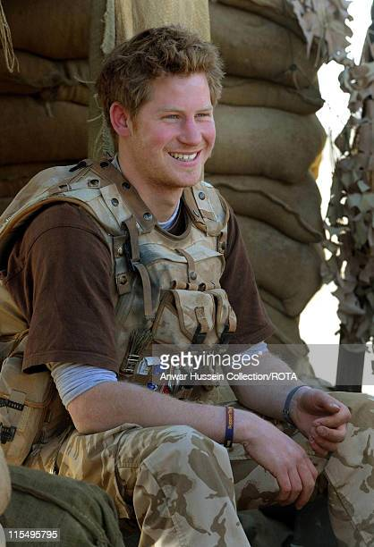 Prince Harry smiles as he sits at the observation post on JTAC Hill on January 2 2008 in Helmand Province Afghanistan