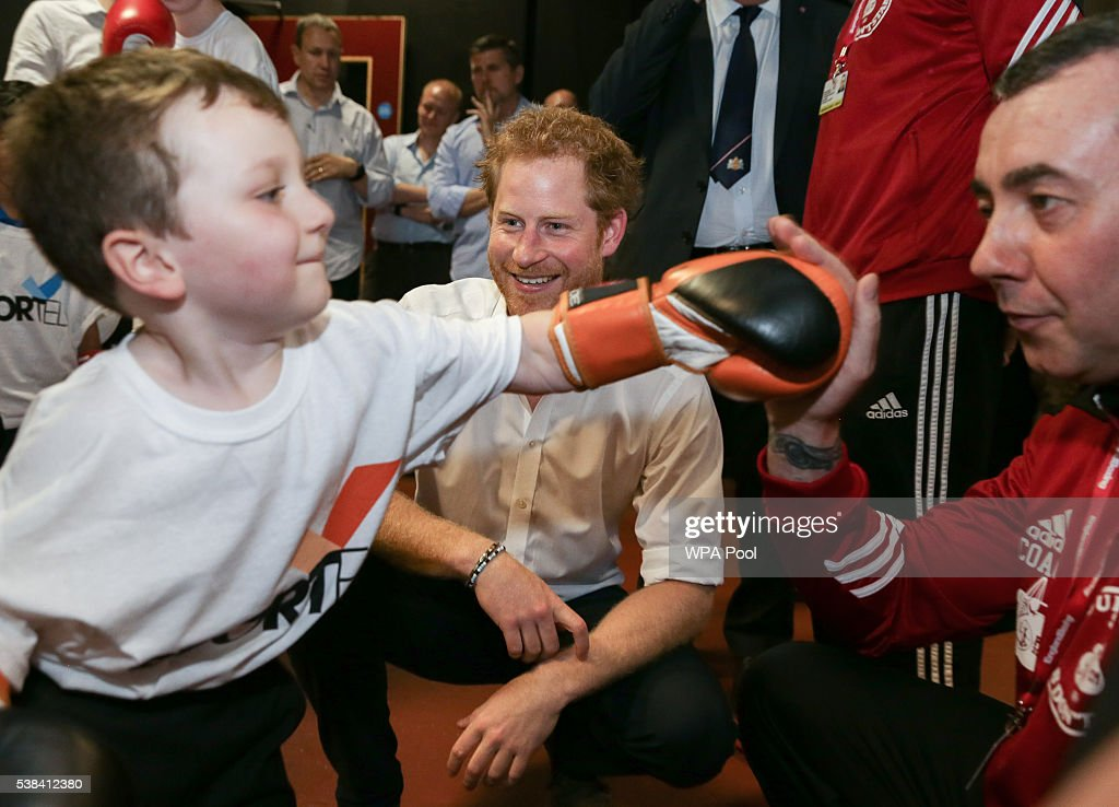 Prince Harry (C) smiles as he watches a young trainee during a visit to the Double Jab Boxing Club to support Sport for Social Development initiatives on June 6, 2016 in London, United Kingdom.