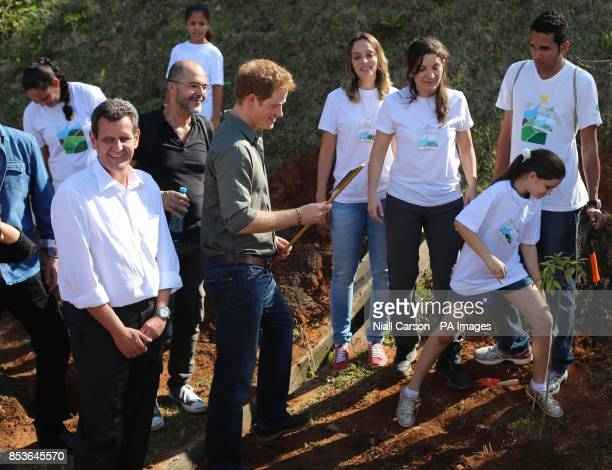 Prince Harry smiles at a miss spelled sign saying Prince Henry as he plants a tree at Cota 200 outside Sao Paolo where he viewed Mata Atlantica the...