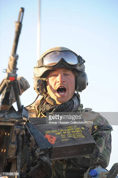Prince Harry speaks on the radio from the turret of his Spartan armoured vehicle in the desert on February 20, 2008 in Helmand Province, Afghanistan.