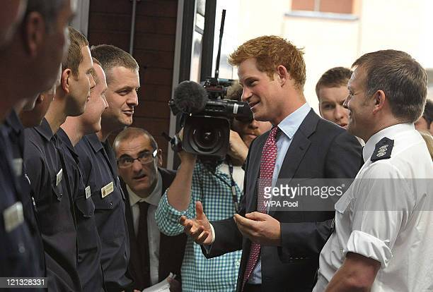 Prince Harry speaks to firefighters at Salford Fire Station who were on duty during last week's riots on August 18 2011 in Salford England Prince...