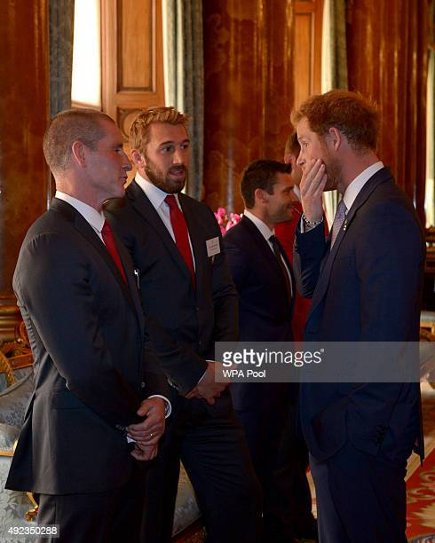 Prince Harry speaks with England Rugby Union head coach Stuart Lancaster and England captain Chris Robshaw during a reception to mark the Rugby World...