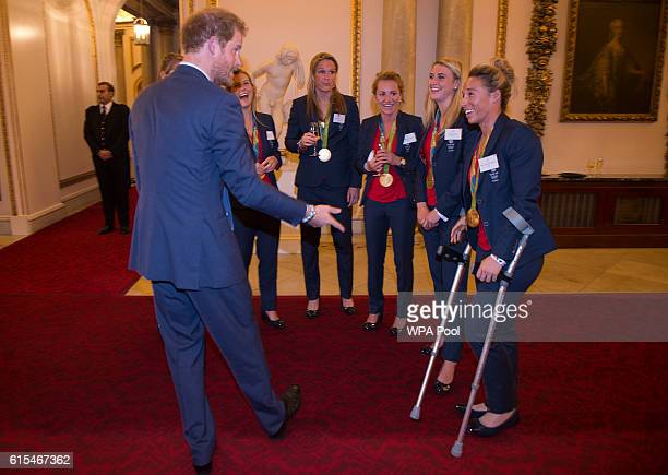Prince Harry speaks with Ladies Hockey Team with Susannah Townsend on crutches at a reception for Team GB's 2016 Olympic and Paralympic teams at...