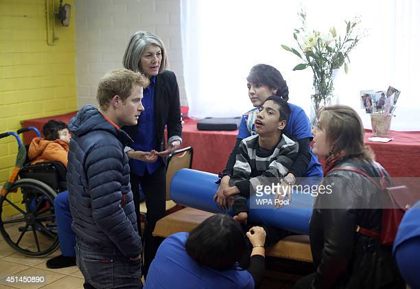 Prince Harry speaks with staff and children at the Fundacion Amigos de Jesus day care centre where they look after children with mental and physical...