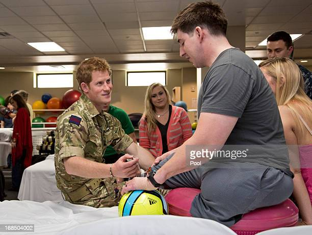 Prince Harry speaks with Staff Sgt Timothy Payne who lost his legs in an IED explosion in Afghanistan during his visit to the Military Advanced...