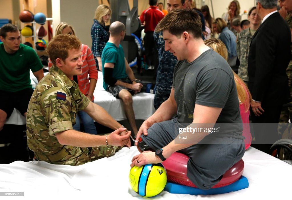 Prince Harry speaks with Staff Sgt. Timothy Payne (R), who lost his legs in an IED explosion in Afghanistan during his visit to the Military Advanced Training Center at Walter Reed National Military Medical Center treating wounded soldiers undergoing physical therapy on May 10, 2013 in Bethesda, Maryland. HRH will be undertaking engagements on behalf of charities with which the Prince is closely associated on behalf also of HM Government, with a central theme of supporting injured service personnel from the UK and US forces.