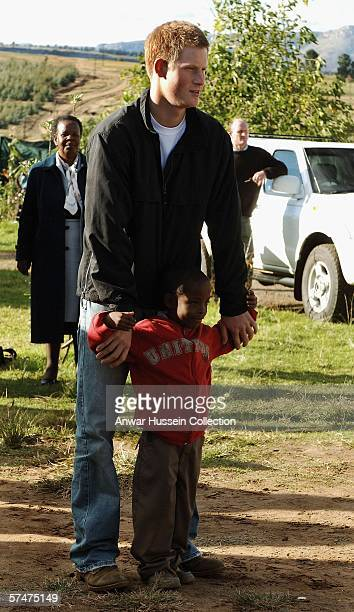 Prince Harry stands with an old friend, Mutsu Potsane, in the grounds of the Mants'ase children's home while on a return visit to Lesotho on April...