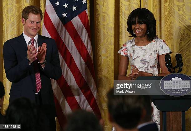 Prince Harry stands with first lady Michelle Obama during an event to honor military families at the White House on May 9 2013 in Washington DC...