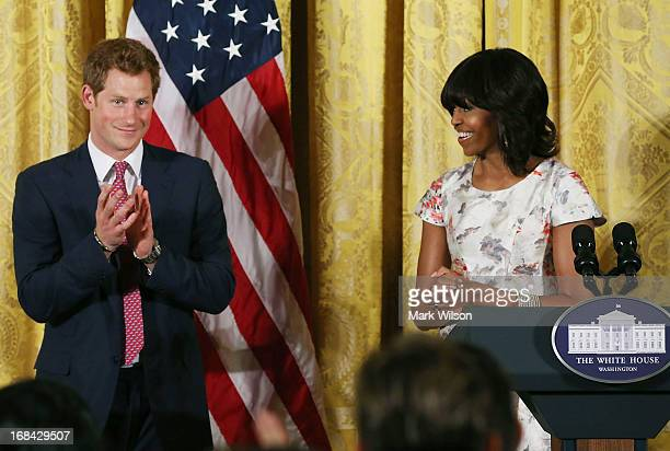 Prince Harry stands with first lady Michelle Obama during an event to honor military families at the White House on May 9 2013 in Washington DC HRH...