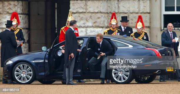 Prince Harry steps out of his Jaguar car as he arrives to watch Queen Elizabeth II present new Standards to the Household Cavalry at Horse Guards...
