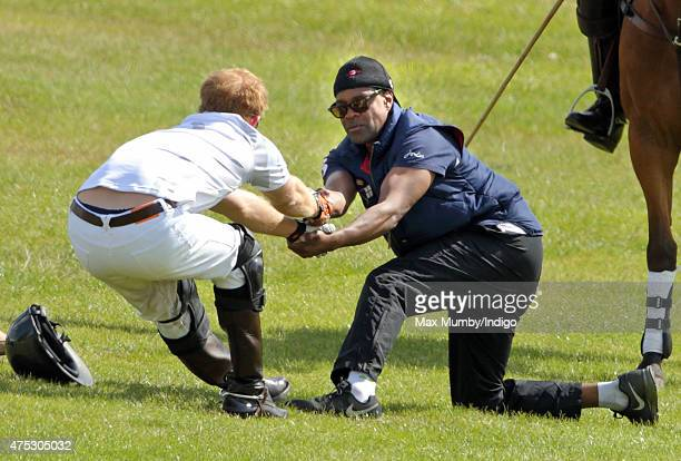 Prince Harry stretches during a break in play on day 1 of the Audi Polo Challenge at Coworth Park on May 30 2015 in Ascot England