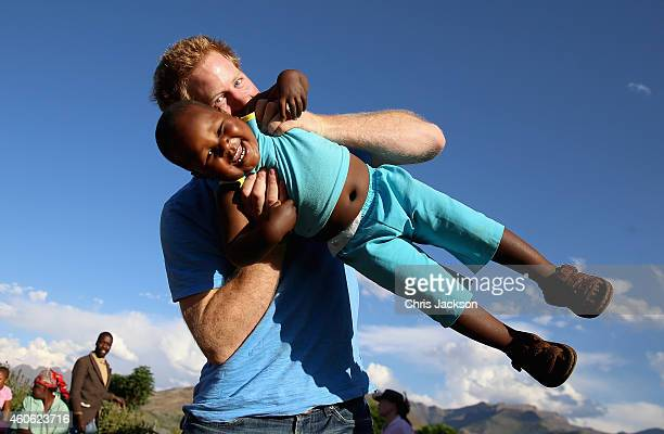 Prince Harry swings young three year old orphan boy called Lerato in this photograph taken with the help of a three year old blind girl called Karabo...
