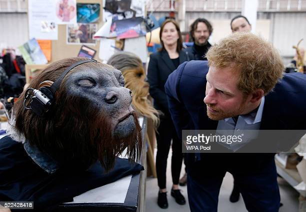 Prince Harry takes a closer look at a robotic mask during a tour of the Star Wars sets at Pinewood studios on April 19 2016 in Iver Heath England...