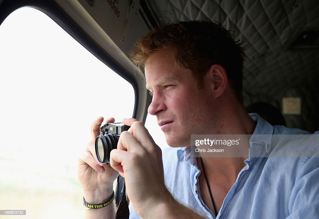Prince Harry takes a photograph out of the window of a Lesotho Army Helicopter on a Fuji X100s Camera as he travels over the Muluti Mountains on the way to a herd boy night school constructed by Sentebale on December 8, 2014 in Mokhotlong, Lesotho. Prince Harry was visiting Lesotho to see the work of his charity Sentebale. Sentebale provides healthcare and education to vulnerable children in Lesotho, Southern Africa. Speaking of the opportunity to document the visit himself, Prince Harry said: 'I have always enjoyed photography and the challenges that come with trying to capture the perfect shot, although privately I don't take many photos. The best photos I have are in my head - I have some very special memories, mostly from Africa. But on this visit, I had the time and opportunity to be on the other side of the camera and take some photos in the stunning country of Lesotho for my charity Sentebale.'