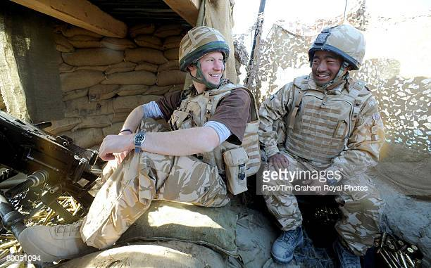 Prince Harry talks to a Gurkha after firing a 50mm machine gun at Taliban fighters from the observation post at JTAC Hill close to FOB Delhi on...