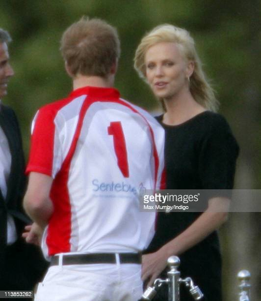 Prince Harry talks with Charlize Theron after playing in the Audi Polo Challenge polo match for team Sentebale versus team Audi at Coworth Park Polo...
