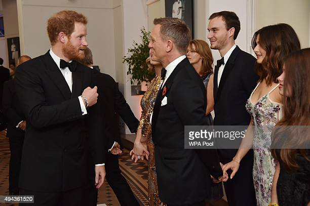 Prince Harry talks with Daniel Craig while attending The Cinema and Television Benevolent Fund's Royal Film Performance 2015 of the 24th James Bond...