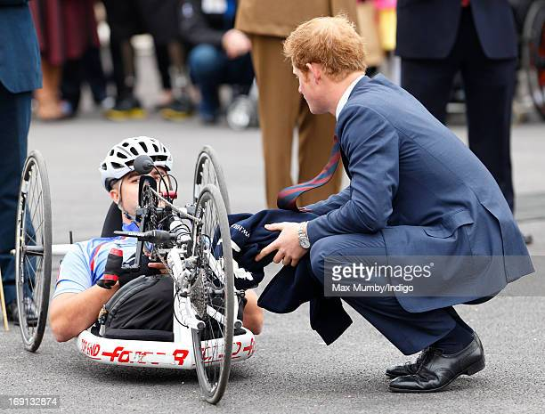 Prince Harry talks with injured US veteran Corporal Charlie Lemon who is taking part in the 2013 Hero Ride on a recumbent hand bike as he and Prince...