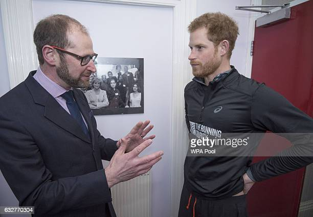Prince Harry talks with Martin HoughtonBrown Chief Executive of Depaul UK by a photograph of his mother Princess Diana during a visit to The Running...