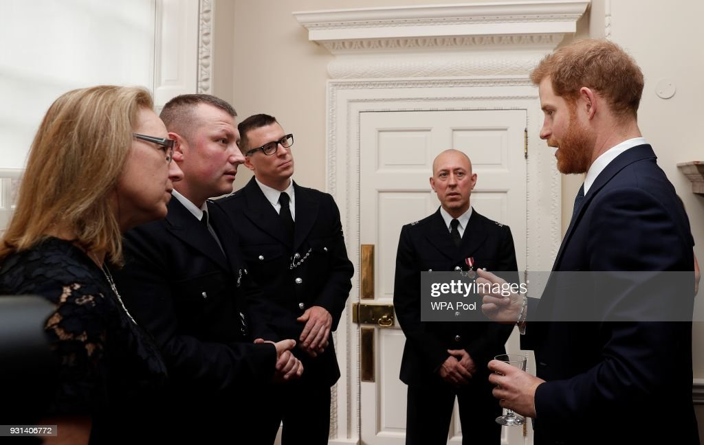 Prince Harry talks with Metropolitan Police officers as he and Prince William, Duke of Cambridge host the winners of The Met Excellence Awards at Kensington Palace on March 13, 2018 in London, England.