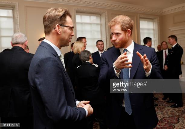 Prince Harry talks with MP Tobias Ellwood who recieved a police bravery award as he and Prince William Duke of Cambridge host the winners of The Met...