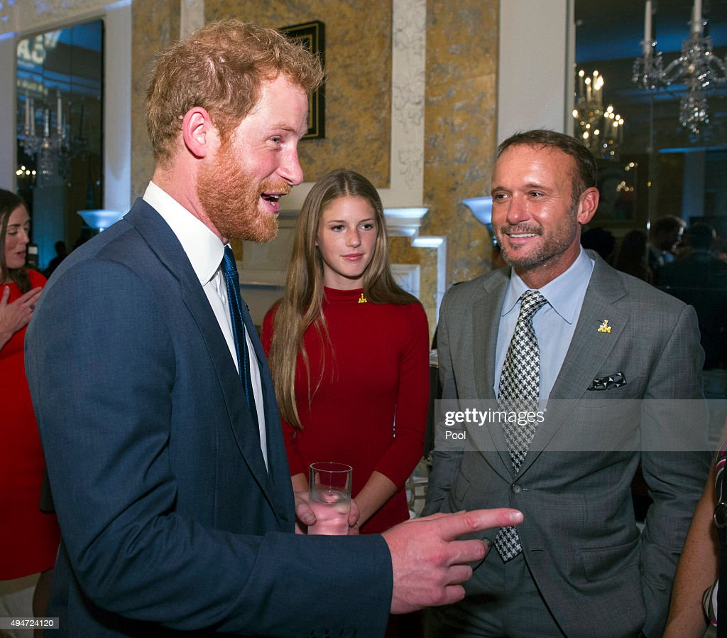 Prince Harry (L) talks with singer Tim McGraw (R) and his daughter Maggie (C) during an Invictus Games reception at the British Ambassador's Residence on October 28, 2015 in Washington DC.