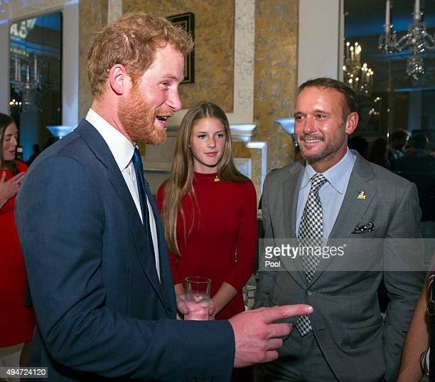 Prince Harry talks with singer Tim McGraw and his daughter Maggie during an Invictus Games reception at the British Ambassador's Residence on October...