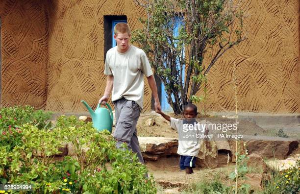 Prince Harry the younger son of Britain's Prince Charles leads young orphan Mutsu Potsane by the hand to plant a peach tree together at the Mants'ase...